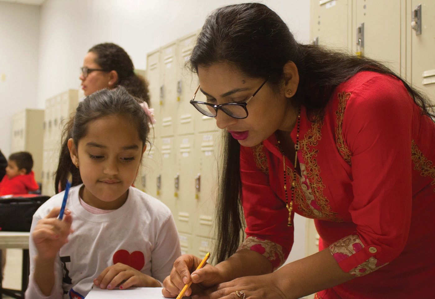 The Nepalese Language School was created by Lions to help children learn about their culture and build confidence. Volunteer teacher Sabitri Joshi, right, helps Sofie Ghimire learn the Nepalese alphabet. Photo by Katya Cengel.