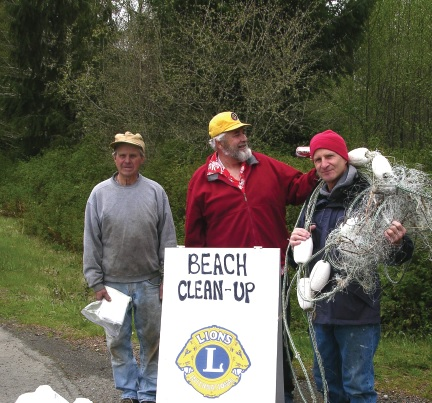 Lions Emil Person and Roy Morris with their helper, Paul Blake, clean up debris along the Strait of Juan de Fuca in Washington.