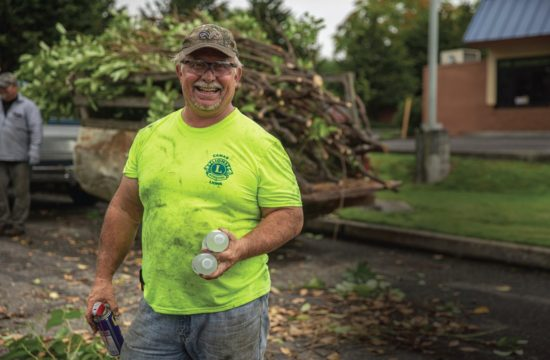 Camas Lions Club member Brian Scott takes a break to smile during his clubs' clean up at the Inter-Faith Treasure House in Washougal. PHOTO BY JACOB GRANNEMAN
