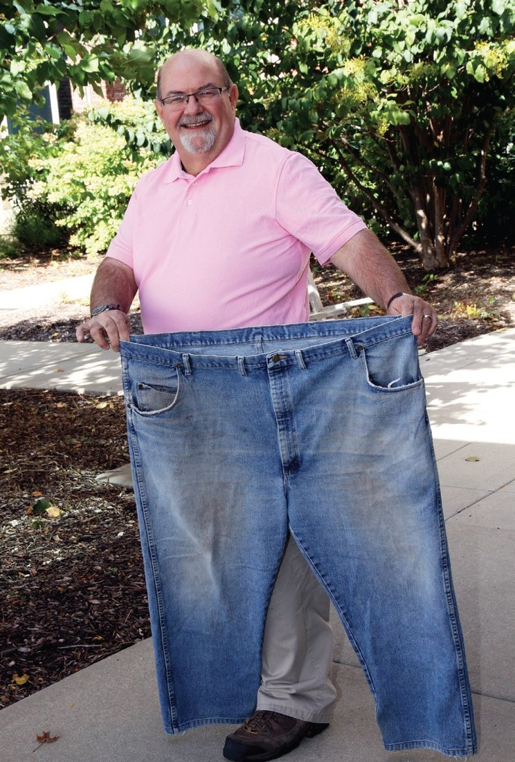 "Len Dompke holds up the pants he wore to his very first ""Jumpstart Your Health"" class. Dompke is grateful to Lions for the support he needed to make lasting changes. Photo courtesy of Edward-Elmhurst Health."