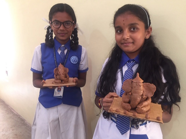 Two students present their versions of the environmentally friendly clay Ganesha idols.