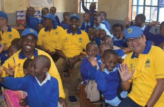 Lions and Johnson & Johnson Vision team members spend time with children at a vision screening in Kenya.