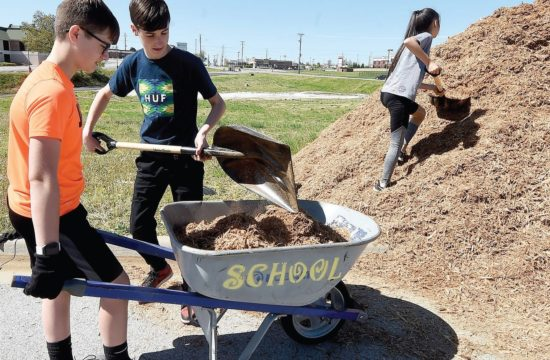 Carl Junction Leos Alex Brownstein, Jackson Hinderliter, and Madeleine Garoutte work on a landscaping project at Irving Elementary School in Joplin, Missouri. Photo by Laurie Sisk/Joplin Globe.