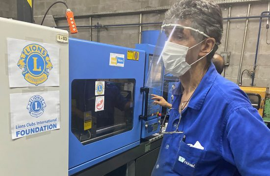 Man stands at machine making Lion face shields