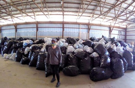 Woman standing in front of bags of cans