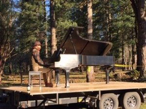 A man plays a piano on top of a flatbed trailer