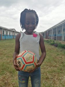 A girl holds a ball specially made for childen who are blind.