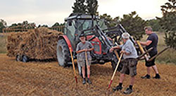 Two men pose next to a tractor in a field
