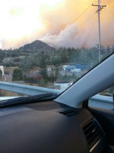 Smoke rises from a mountain outside the front windshield of a car