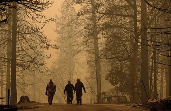 Firefighters walk toward large fire