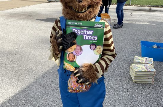 A child in a bear costume holds a Lions Quest workbook
