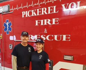 Man and woman stand in front of fire and rescue truck