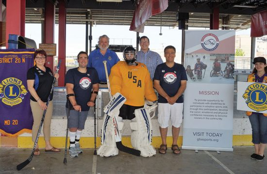 Hockey goalie poses with Lions Club Members