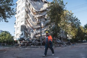 Man walks by a building that has half-collapsed
