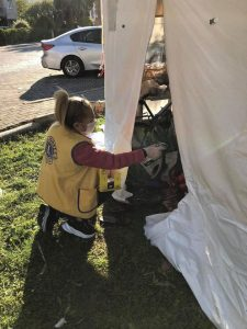 Lion hands supplies to victim in tent