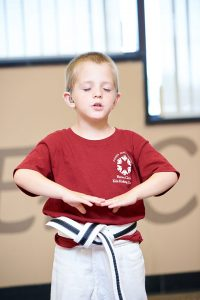 Child stands with hands in front, eyes closed, breathing out.