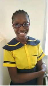 Girl with glasses smiles at camera.