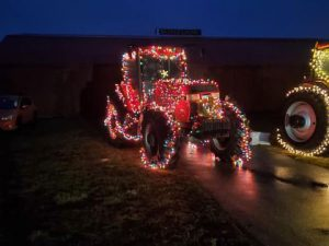 A large tractor covered in Christmas lights.