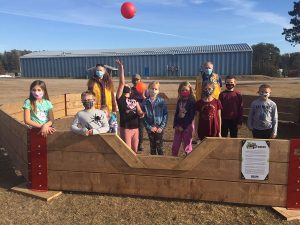 Children celebrate inside a gaga pit