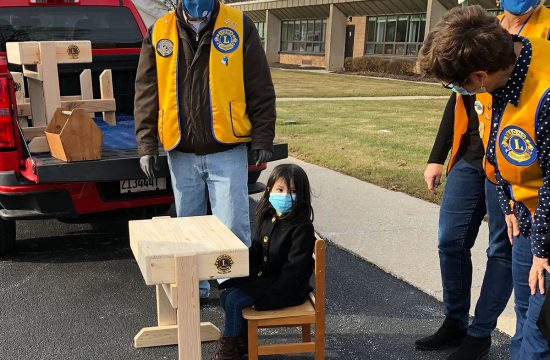 Girl sits at a new school desk built for her by Agawam Lions Club members.