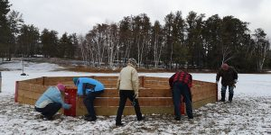 People work on assembling a gaga pit