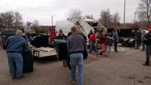 Lions club members load garbage into a truck for local clean up.