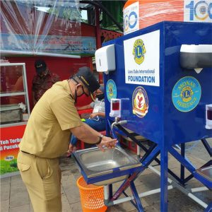 Man washes hands at Lions Clubs handwashing station
