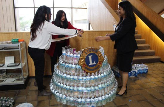 Group of young women making sculpture out of water bottles.