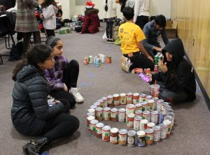 teens creating sculptures from canned goods.