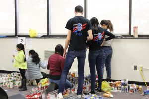 Group of teens working on sculpture of canned goods.