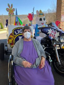 Woman in wheel chair next to Easter bunny.
