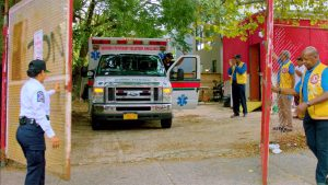 Ambulance with door open and Lions Club member clapping