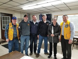 Lions CLubs INternational members stand with woman with orcam glasses and special cane