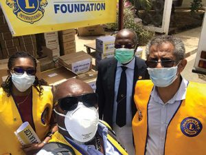 Lions club members with yellow vests and white face masks, looking at camera.