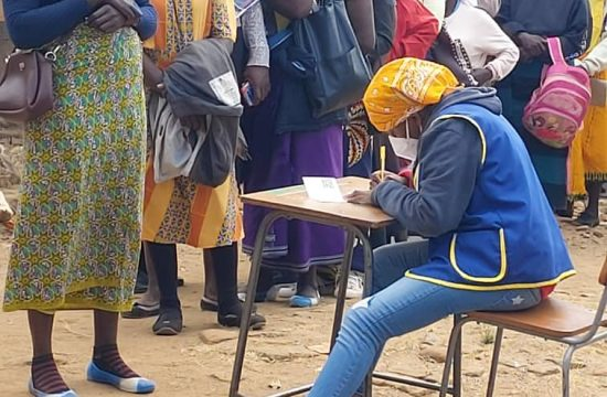 Lions Club member checks in woman for vaccine