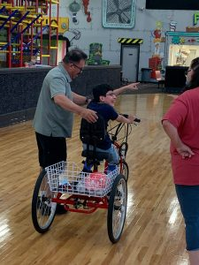 boy on tricycle with man helping guide him.
