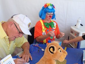 Woman in clown costume and man in Lions Club hat.