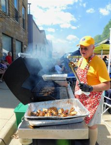 Man working the grill in Lions Club hat