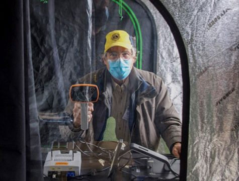 Man in Lions Club hat looks through tent window